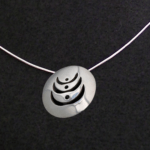 Photograph of the pendent necklace representing women supporting women.